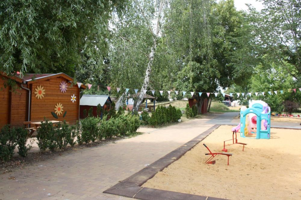 Außenansicht in Richtung Grünanlage mit kleiner Sandkiste im Vordergrund, Kinderland-Ringleben e.V.
