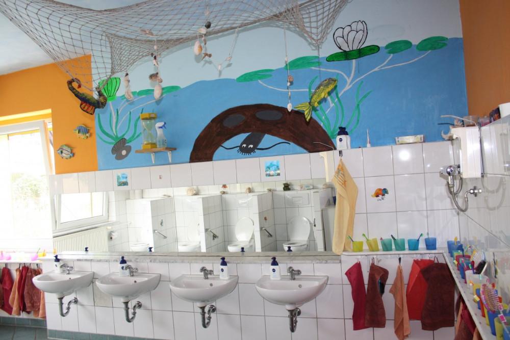 Innenansicht, Bad mit Spiegel und Waschbecken, darüber ein Unterwasserbild, Kinderland-Ringleben e.V.